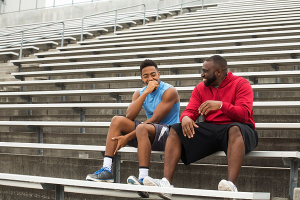 Teen athlete and his coach sitting in bleachers laughing. Represents a talented teen athlete receiving neurofeedback in katy texas 77494. Also represents a talented teen athlete and neurofeedback in houston texas.