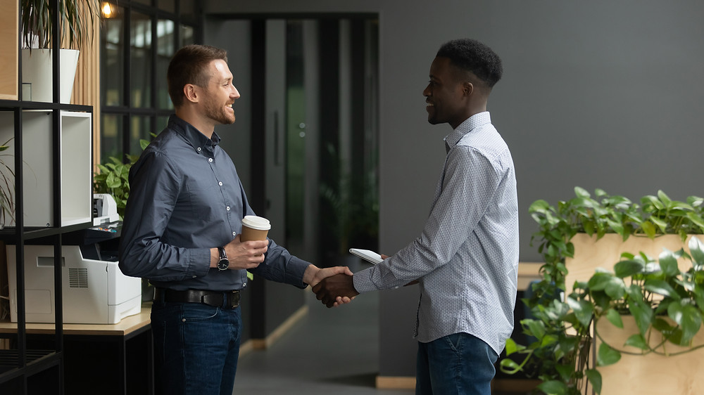 White male shaking the hand of a black male. Represents teen depression counseling in katy tx. Also represents neurofeedback for ptsd houston tx.
