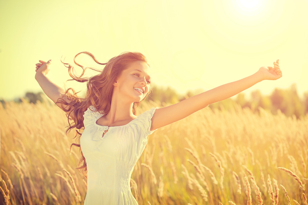 Smiling teen girl with arms raised in a field. Represents counseling for teenagers in katy texas 77494. Also represents teen EMDR for teen katy, texas and EMDR for teens in Houston Texas.
