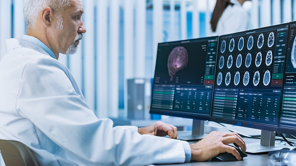 Doctor looking at brain scans on computer. Represents neurofeedback for ptsd katy texas. Also represents neurofeedback for anxiety katy texas 77494.