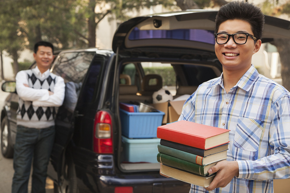 Asian young adult in glasses holding books with dad leaning against car in the background. Represents the need for young adult therapy katy, tx 77494. Also represents the need for young adult therapists katy, tx 77494.