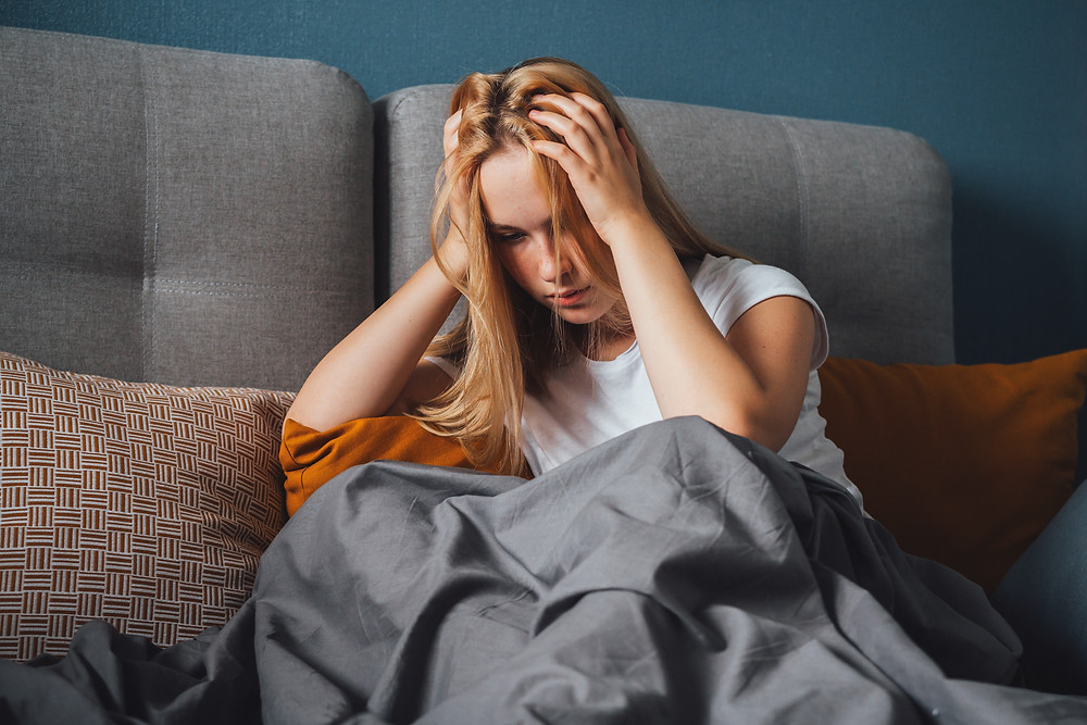 Young adult woman sitting on couch, under blanket, hands on her head looking sad. Represents the need for therapists for young adults katy, tx 77494.