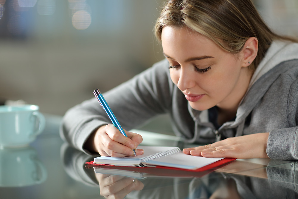 Teen girl writing in notebook. Represents the need for emdr for teens katy, tx 77494. Also represents the need for neurofeedback in katy, tx 77494 and houston.