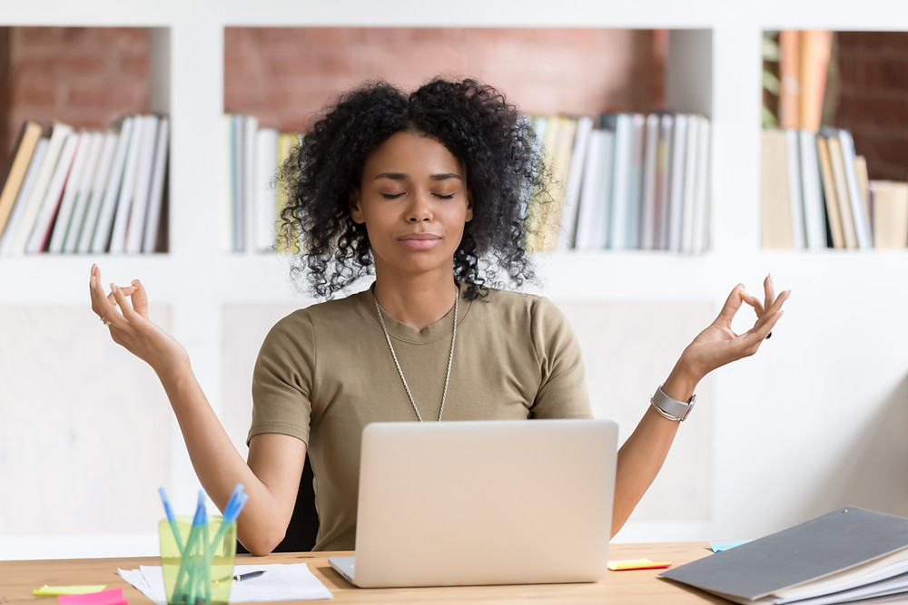 Black woman in front of laptop in meditation pose. Represents the need for young adult counseling katy, tx and counseling for young adults katy, tx 77494.