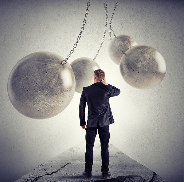 Man looking down cracked pathway with wrecking balls in swinging. Represents man seeking counselor katy texas 77493. Man could be looking for counselor houston texas.