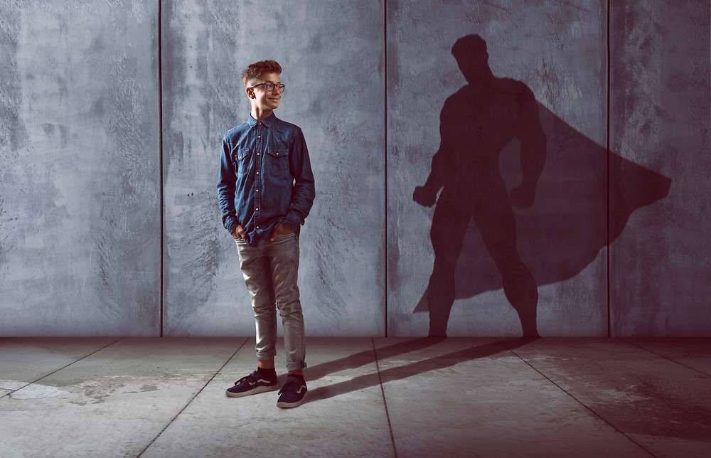 Teen boy with glasses looking at his shadow that looks like superman. Represents the need for teen therapy katy, tx and teen counseling katy, tx 77494. Also represents the need for family therapy katy, tx and family counseling katy, tx 77494.