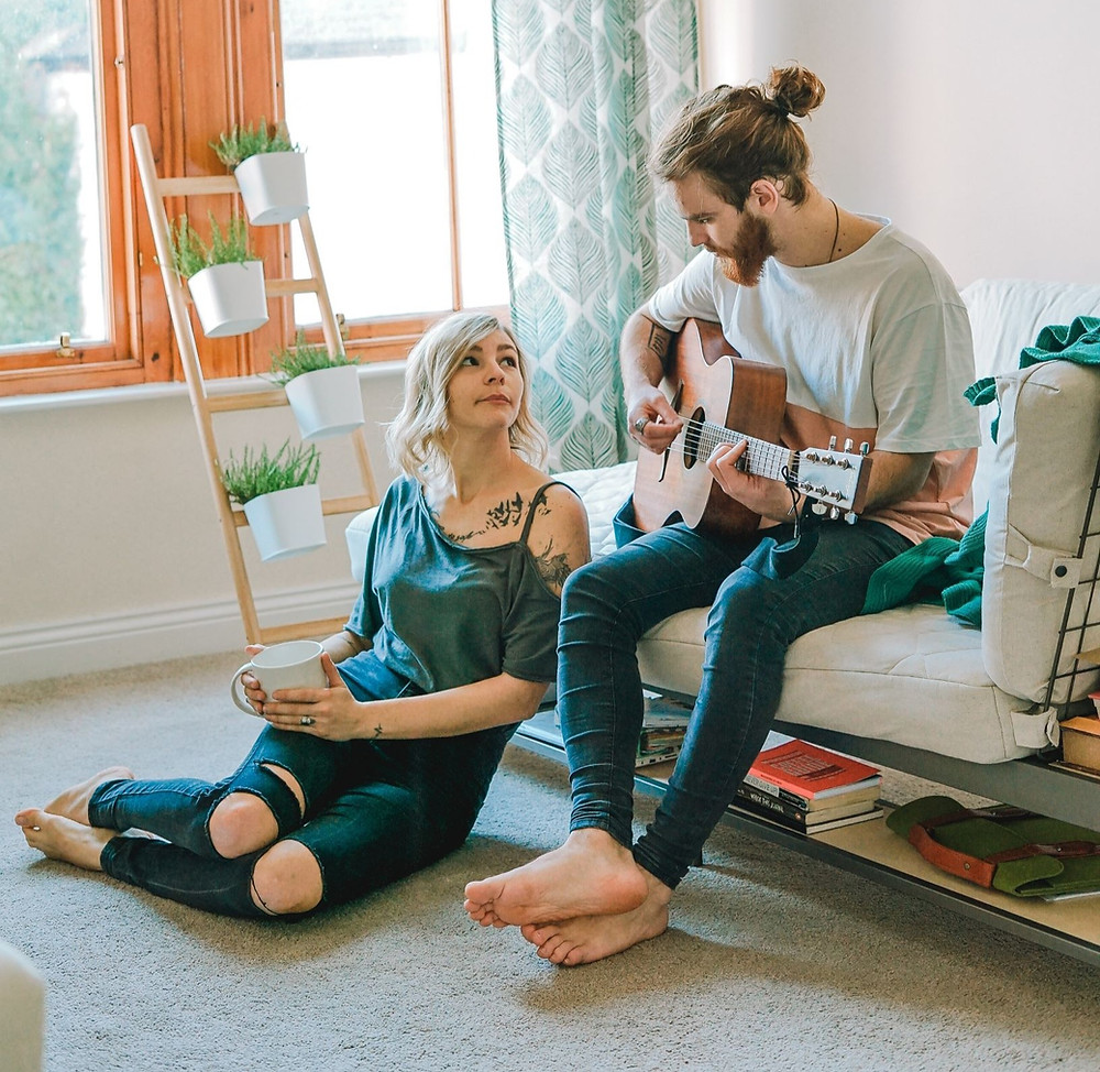 Man playing guitar for woman who is looking at him. Represents the need for marriage counseling katy, tx 77494 and couples therapy katy, tx 77494.