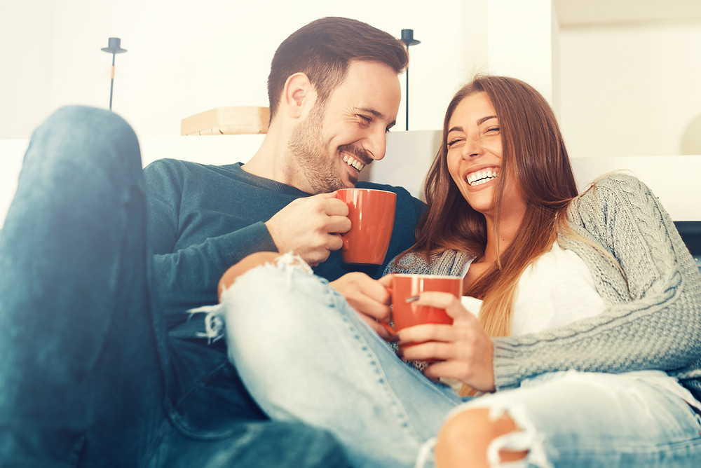 Couple on couch smiling holding coffee mugs. Represents the need for marriage counseling katy, tx 77494.  Also represents the need for couples therapy katy, tx 77494.