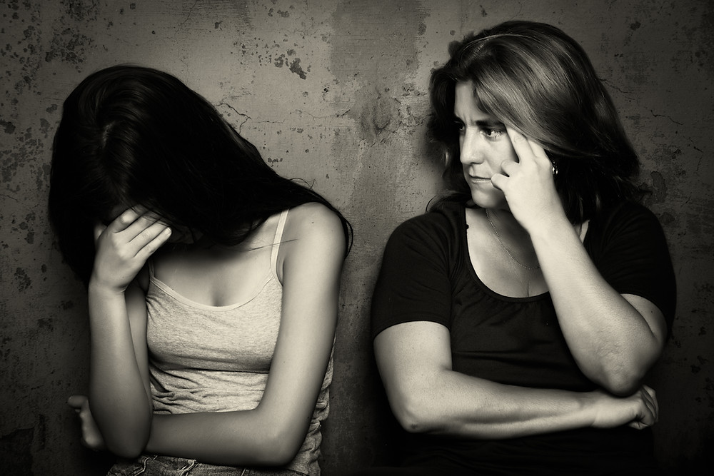 Teen girl with her hand over her eyes & mom looking at her. Represents need for teen depression therapy in Houston Katy 77494