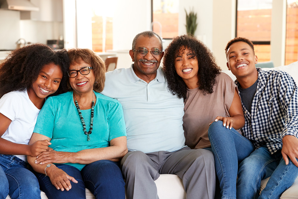Black family sitting on couch smiling. Represents counseling for teens and teen family counseling in katy tx 77494. Also represents counseling for teens and family therapy in houston tx.