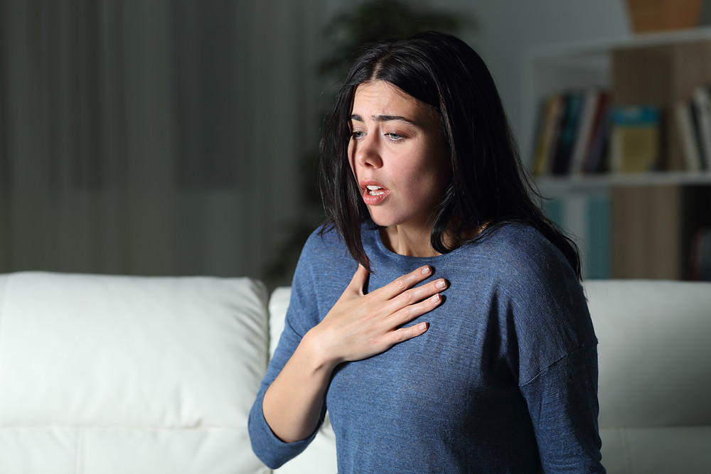 Woman looking afraid holding her hand on her chest. Represents the need for anxiety treatment katy, tx and neurofeedback for anxiety houston, texas.