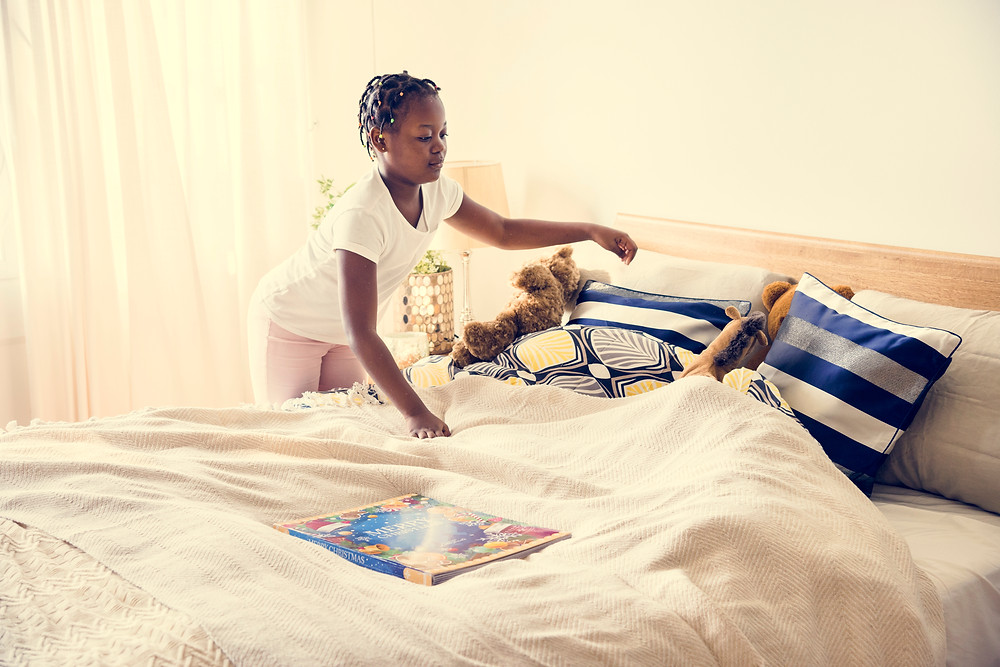 Black teen girl making her bed. Represents the need for teen therapy for depression katy, tx and teen therapy for anxiety katy, tx 77494. Also represents the need for teen counselor katy, tx 77494.