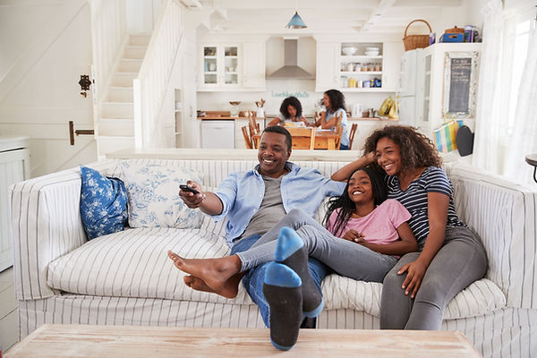 Black family with teen sitting on couch. Represents the need for family counseling katy, tx and counseling for ptsd katy, tx. Also represents the needd for  teen treatment for shame houston, tx.