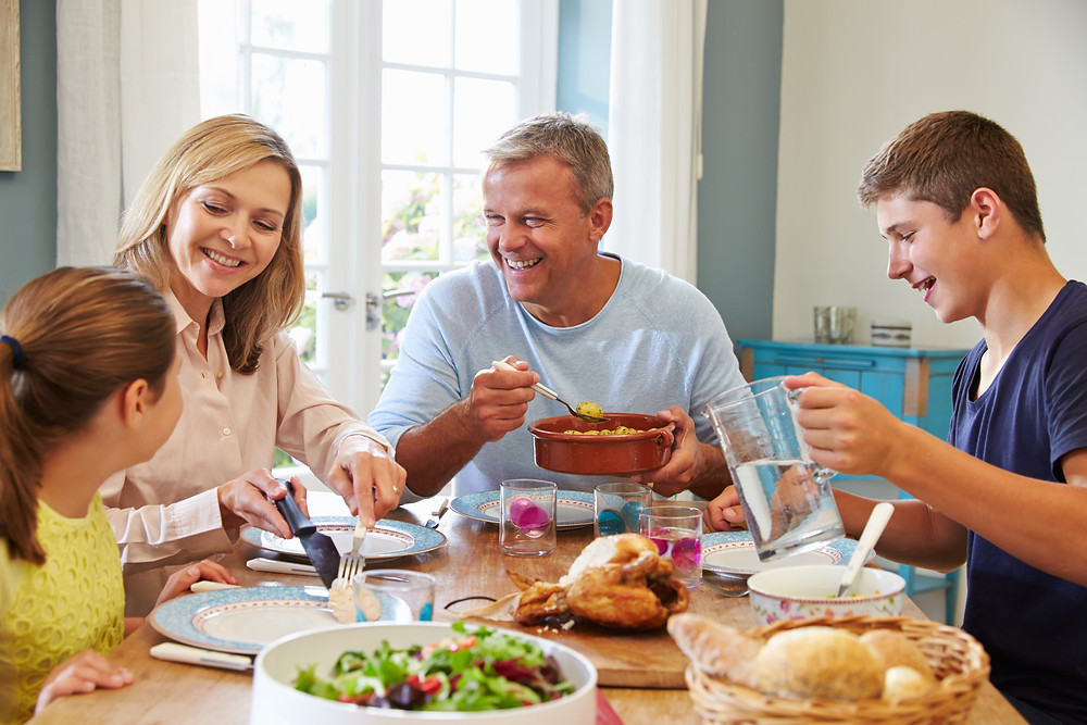 Mom, dad, son, and daughter at the dinner table smiling. Represents the need for family counseling katy tx and family therapy in katy, tx 77494. Also represents the need for teen therapy katy, tx and teen counseling katy, tx 77494.