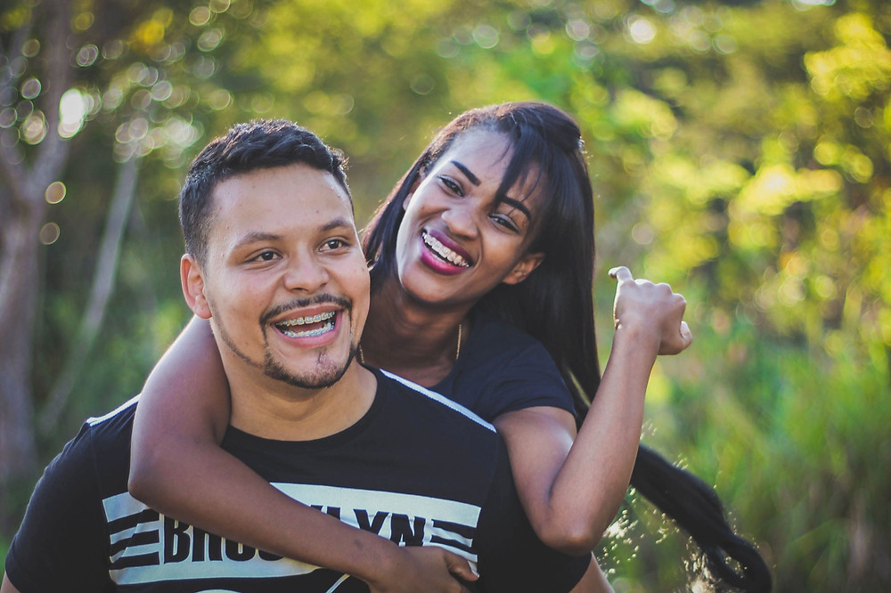 Black woman piggy backing on black mans back. Represents the need for marriage counselor and marriage therapist katy, tx 77494. Also represents the need for couples counseling katy, tx 77494.