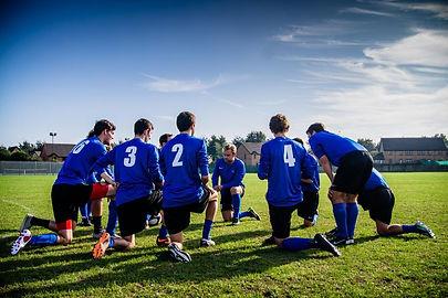 Soccer Team Kneeling Listening to Coach.