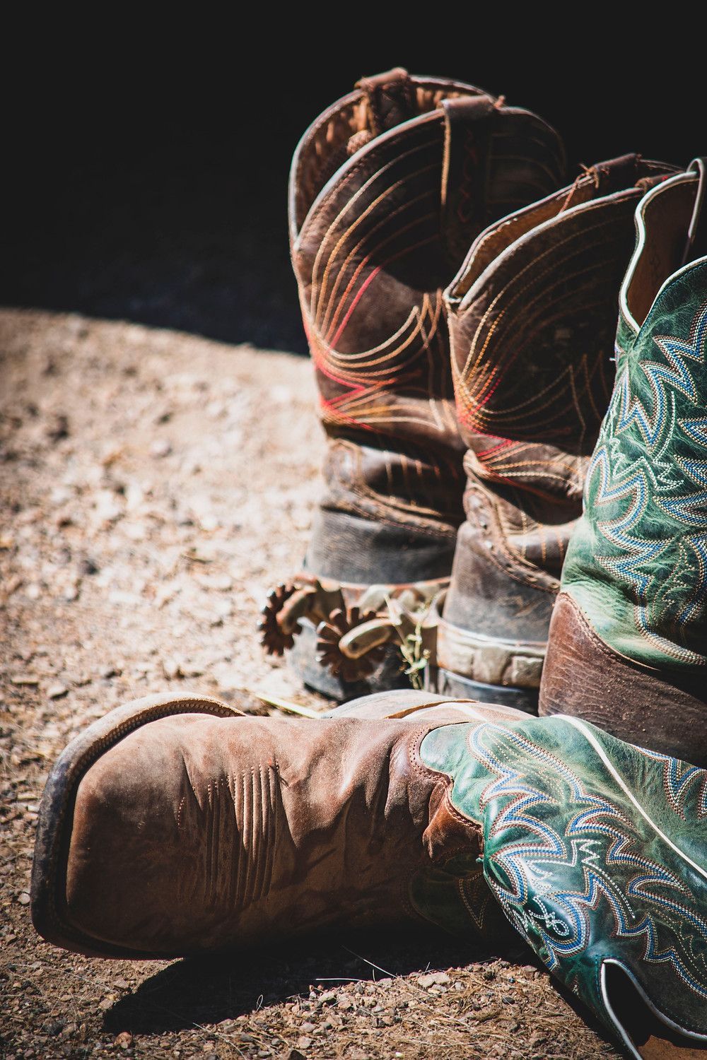 two pairs of worn cowboy boots