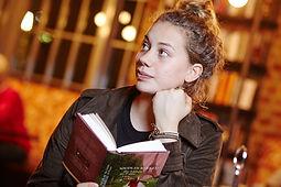 Junge Frau sitzt am Tisch und liest ein Buch
