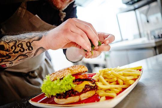 Ein Burger wird in der Küche auf dem Teller angerichtet