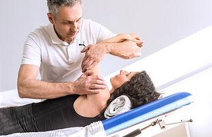 Der Physiotherapeuth Schiemann behandelt eine Patientin am Schultergelenk