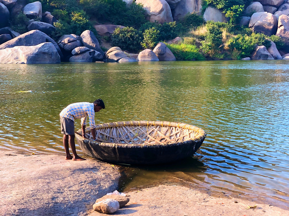 A man tending to his coracle on the waters of a river, with an array of big boulders on the opposite side of the river