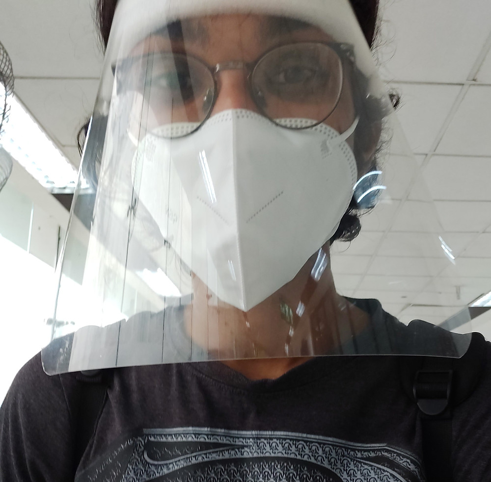 a man wearing a face shield and N-95 mask