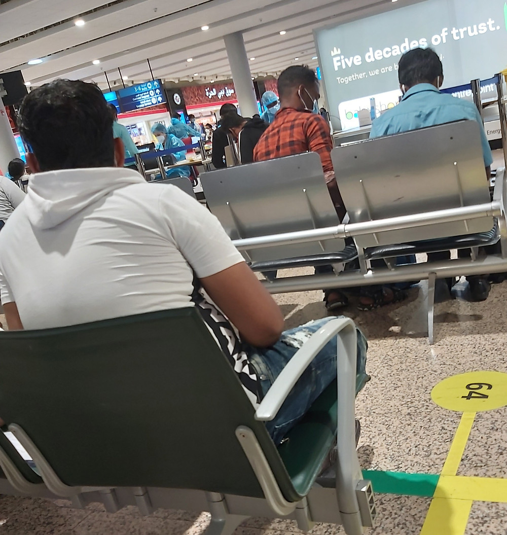 people seated on chairs at Dubai Airport
