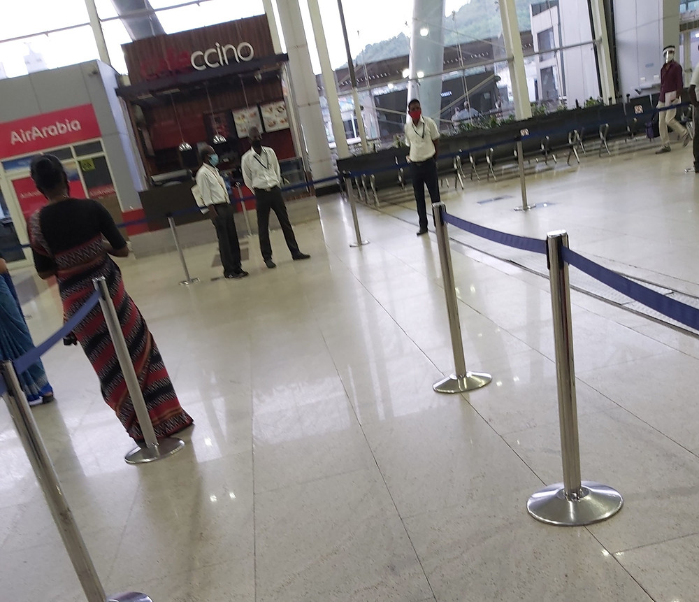 Row of shops closed in an airport, and a few airport officials with protective gear on