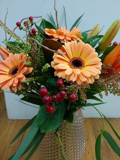 Retro vase along with stunning gerbera's, lilies and seasonal foliages..