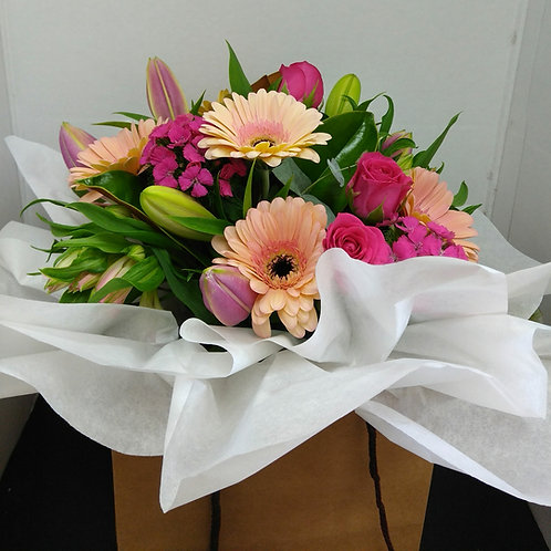 Fresh seasonal blooms includes a vase and presented in a bag.