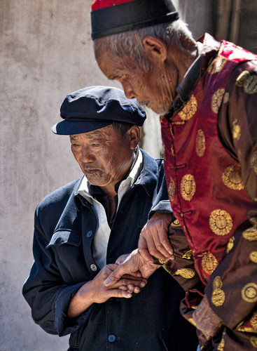 A blind elder is helped by a friend;  Xizhou, China