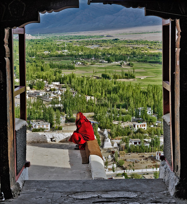 Monk in reflection overlooking the Indus River Valley; Ladakh