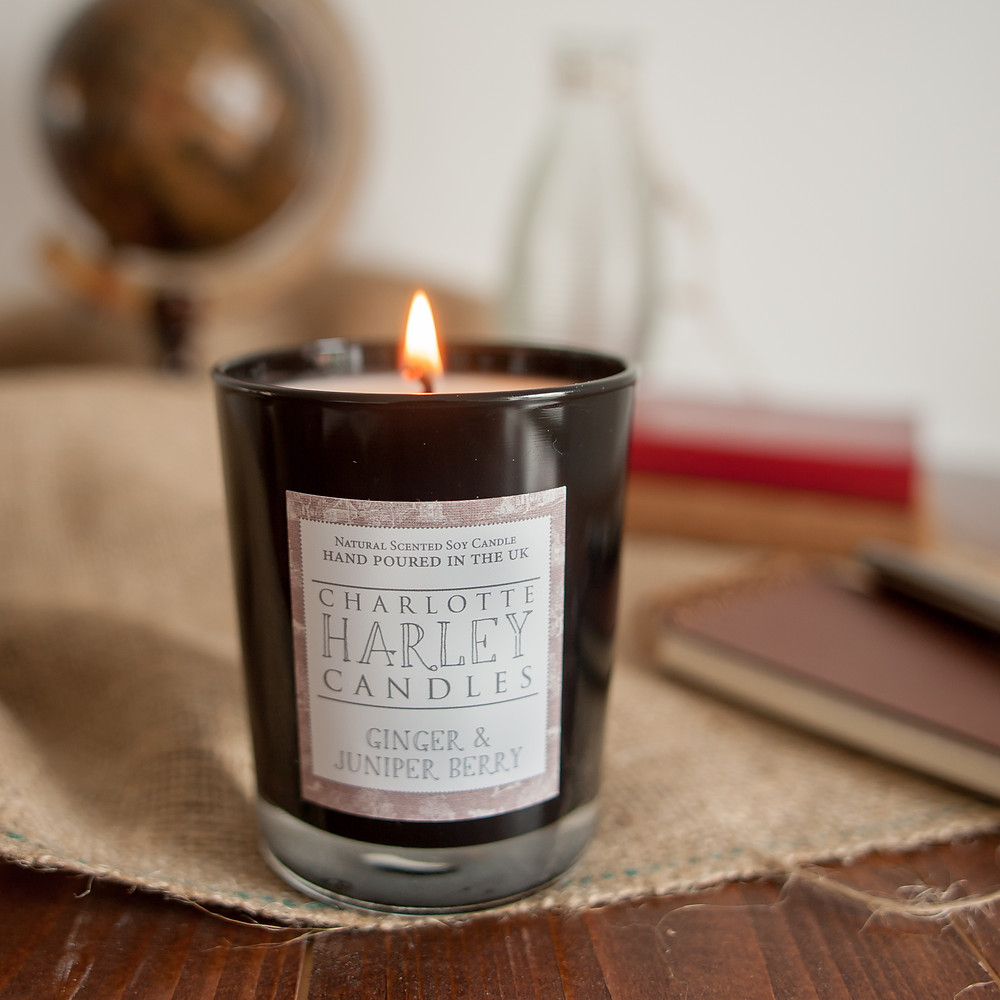 Charlotte Harley Ginger and Juniper candle burning in a black container