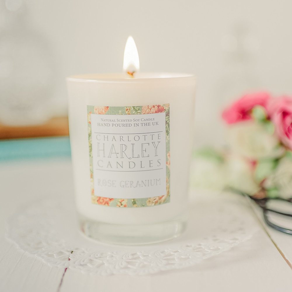 A lit Charlotte Harley Rose Geranium soy wax candle
