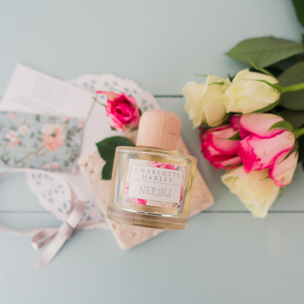 A neroli reed diffuser bottle surrounded by pink and cream roses