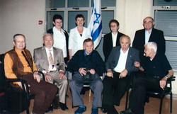 קבוצה של מעפילי אקסודוס לפני טכס הדלקת משואות ביום השואה במכון משואה בתל יצחק  מרדכי רוזמן יושב במרכ