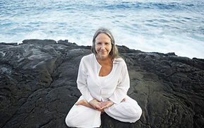 A woman sitting on a large rock by the ocean