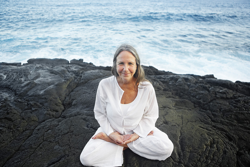 Older Caucasian woman in lotus position in front of ocean waves