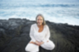 Mature woman in yoga pose on rock by water