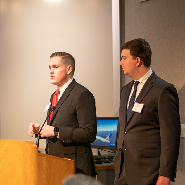 Conference Director Tyler Barry (left) and member Stephen Smith (right) announce the next speaker.