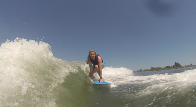Coach Kara surfing