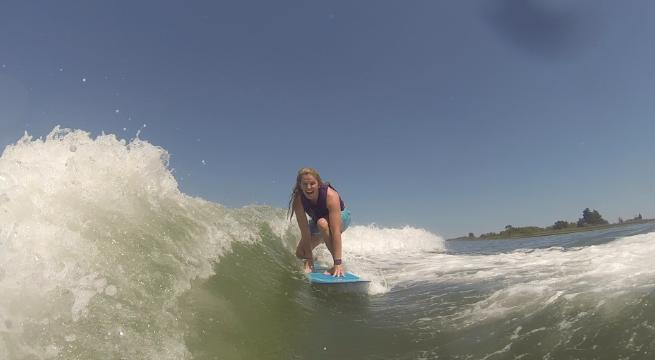 Coach Kara surfing