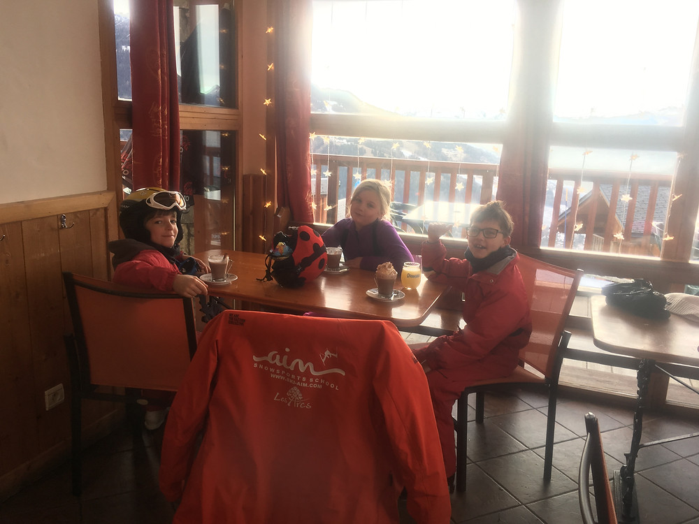 Kids enjoying their ski lessons with a hot chocolate