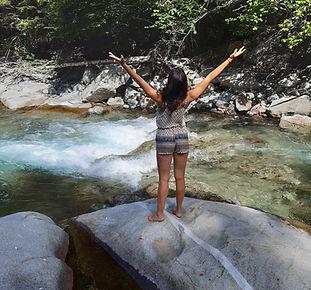 Persona reconectando con la naturaleza y consigo misma encima de una roca en medio de un rio en el valle de Benasque.