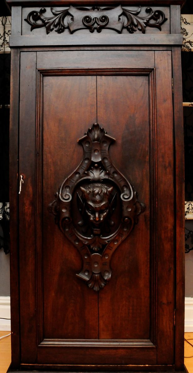 The wardrobe had a strange carving of a demonic head on the front