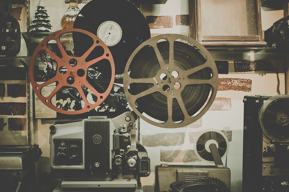 Old style movie projector & big film reels attached.