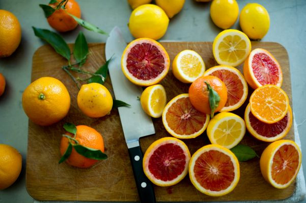 variety of citrus fruits on cutting board