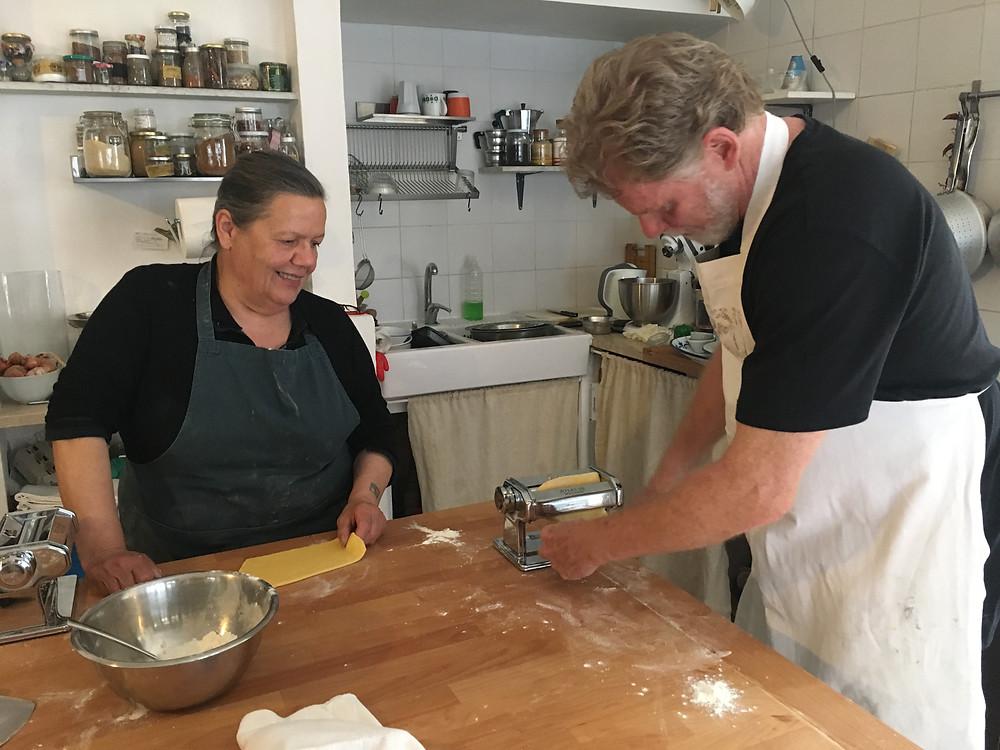 Carla watching Kevin Barnett rolling pasta dough