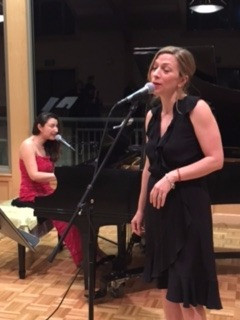 Photo: Jennie Chabon singing, accompanied by Marina at the piano