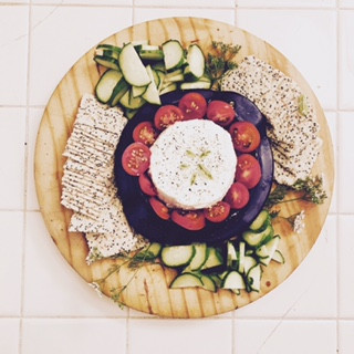 Kefir cheese surrounded by vegetables and crackers